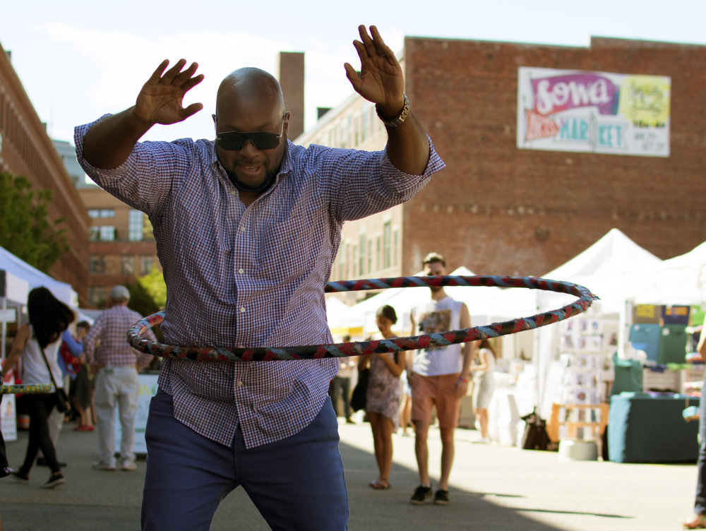 Stefanie catches this pro hula hooper in action. Check out our sweet SoWa sign in the background!