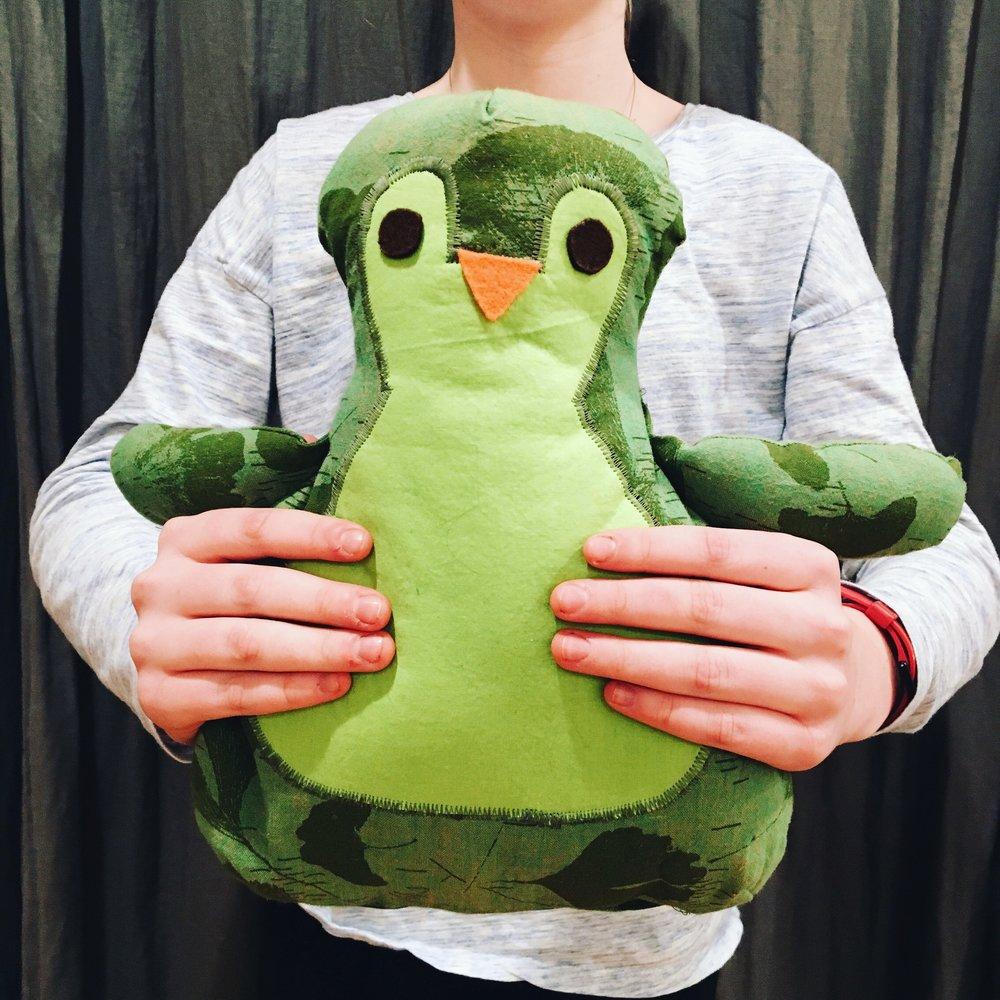 Froggy-hued stuffed penguin.