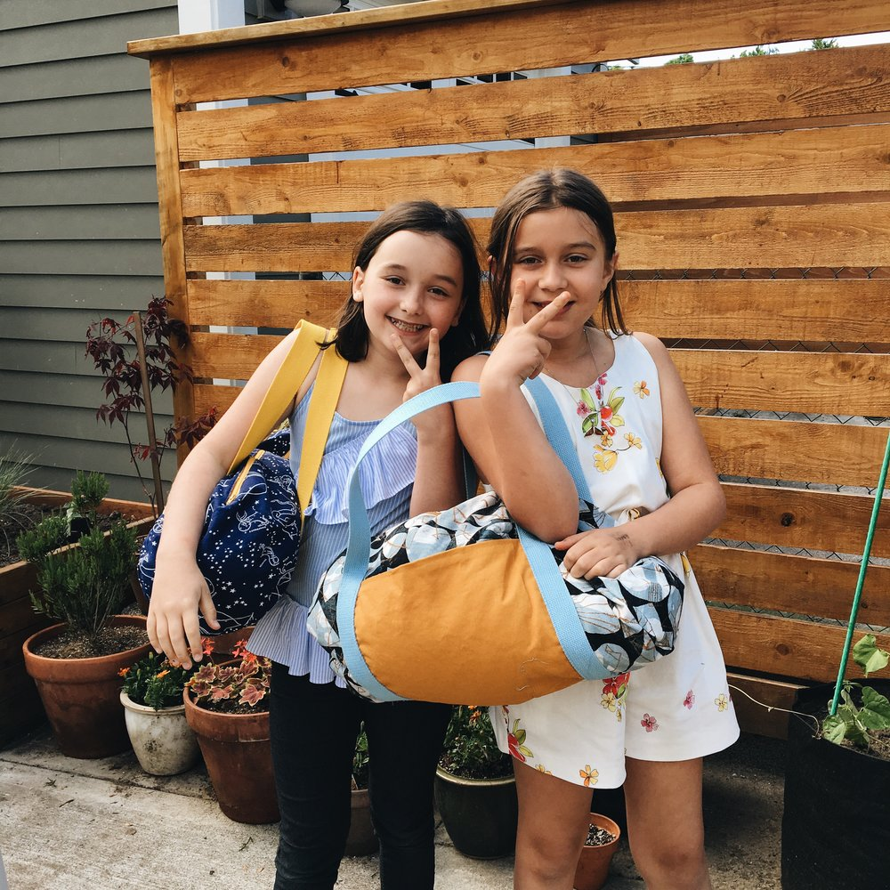 Maia and Anna with their duffle bags.