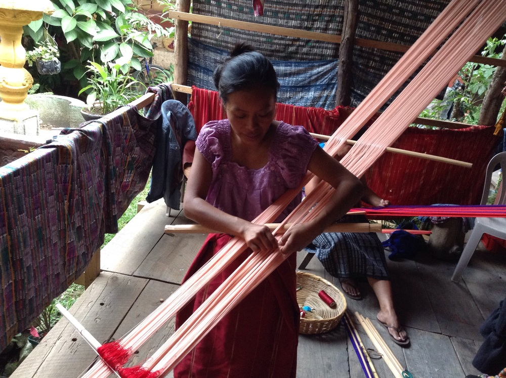 Claudia prepares the back strap loom by combing the threads.