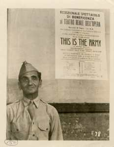 Irving Berlin in his U.S. Army uniform, next to a poster advertising the only civilian performance of his traveling U.S. military play 'This Is The Army' at the Teatro Reale dell'Opera in Rome, Italy, in June 1944. The play was in Rome performing for U.S. military personnel during a tour in World War II [Photograph by: Zinn Arthur]. Courtesy of The State Archives of North Carolina's Military Collection.