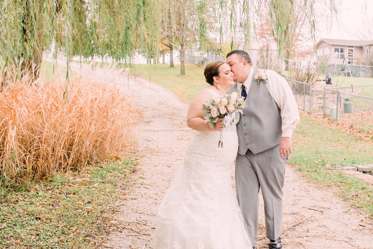 Wedding-Photography_Gatherings-by-Farmhouse-Catering_Nevada-Iowa_Bride-and-Groom-Kissing-cheek-under-willows-iowa+wedding+photographer.jpg
