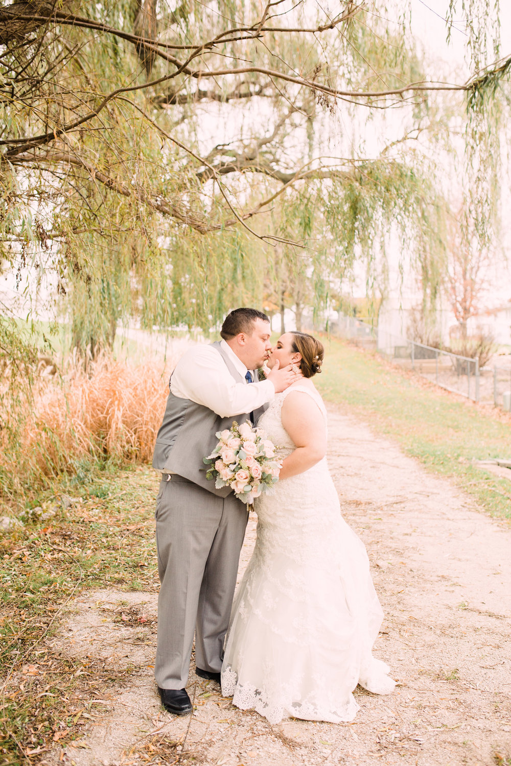 Wedding-Photography_Gatherings-by-Farmhouse-Catering_Nevada-Iowa_Bride+and+Groom+Kissing+under+willows-iowa+wedding+photographer.jpg