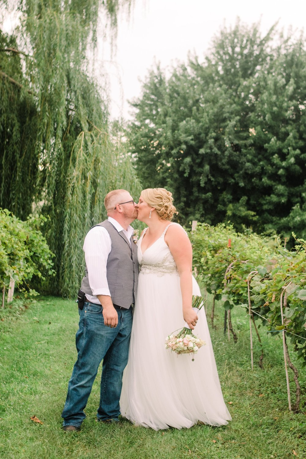 Wedding-Photography_river valley orchard and winery-humboldt-Iowa_kissing in vineyard-iowa+wedding+photographer.jpeg