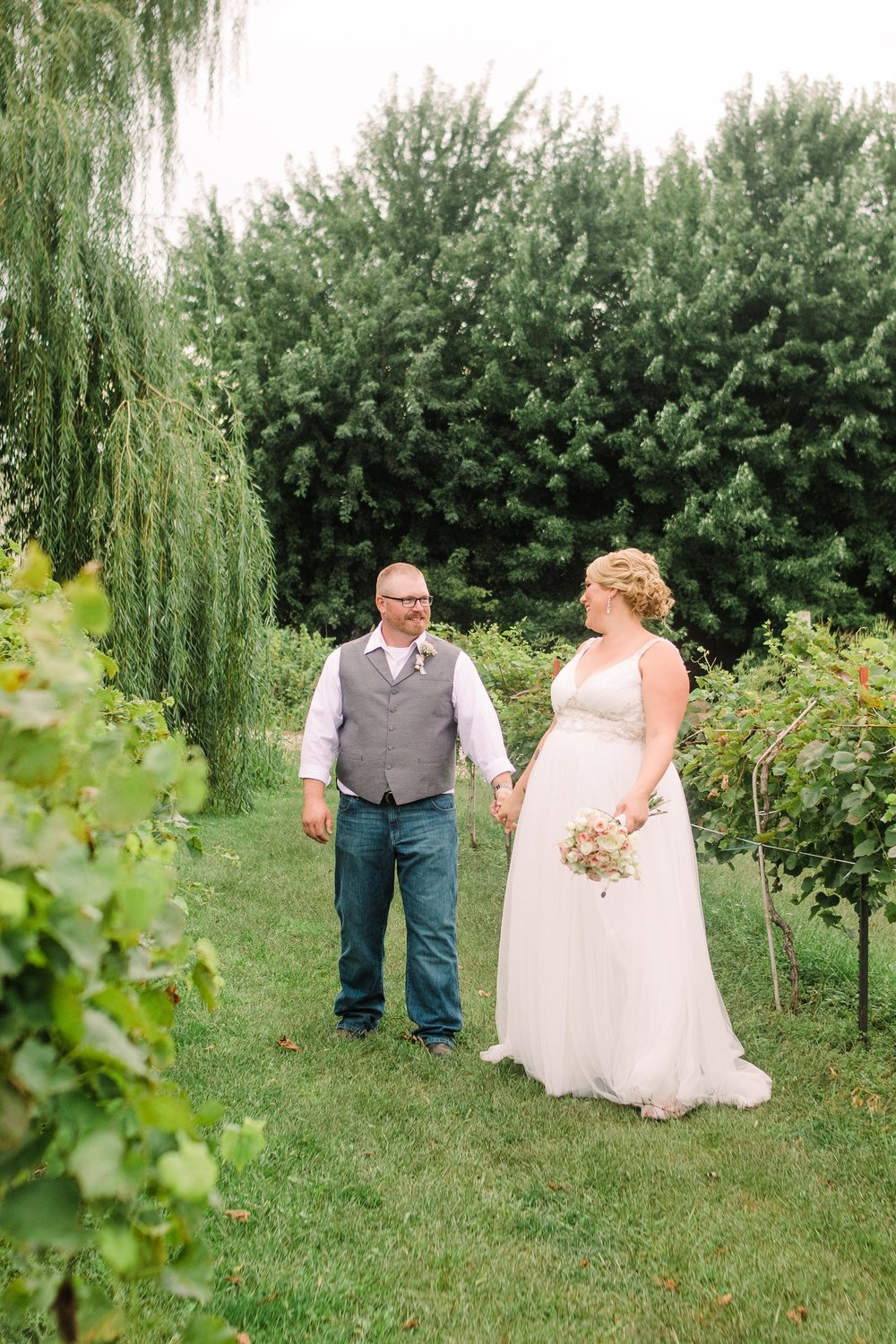 Wedding-Photography_river valley orchard and winery-humboldt-Iowa_walking in vineyard-iowa+wedding+photographer.jpeg