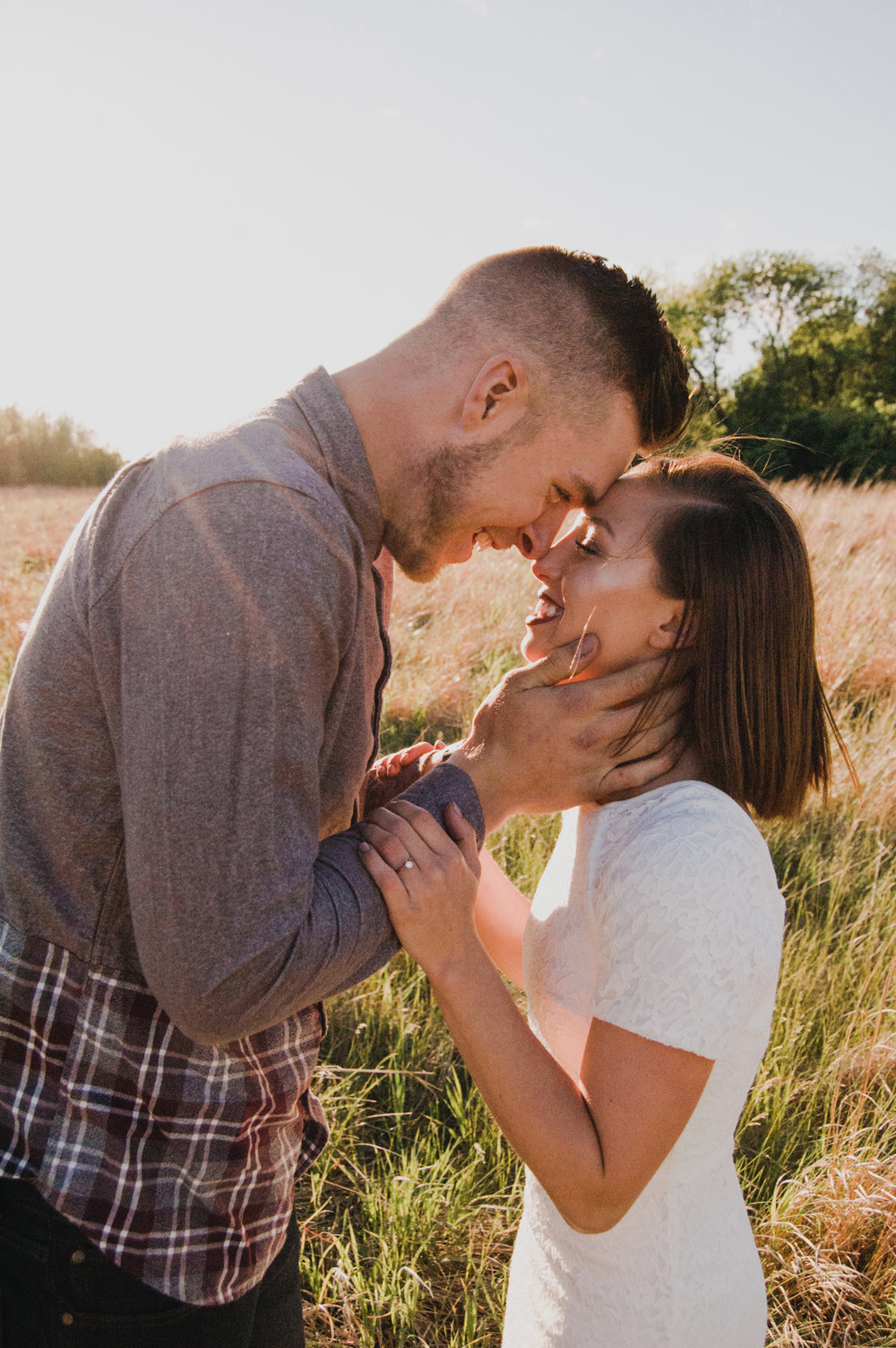 Engagement-Photography-Open-Field-along-Highway-Fort-Dodge-Iowa-embracing-holding-faces-romantic-in-field-at-sunset-iowa+engagement+photographer.jpg