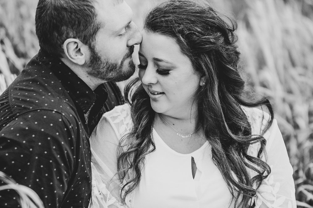 engagement photography-sitting in grass groom kissing brides forehead-brushy creek state recreation area-lehigh-iowa-iowa engagement photographer.jpg