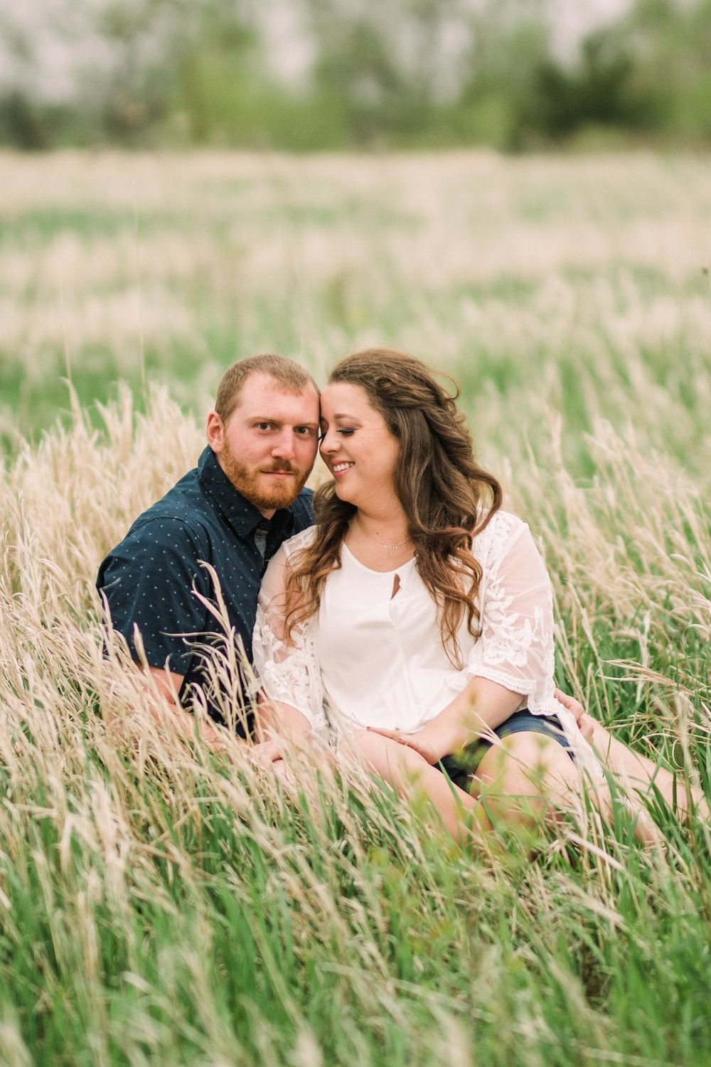 engagement photography-sitting in grass groom looking-brushy creek state recreation area-lehigh-iowa-iowa engagement photographer.jpg