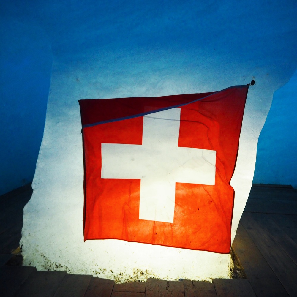 Švýcarská vlajka na konci ledového tunelu Furka, který má převýšení 2 429 m. Zajímavostí je, že se zde natáčela bondovka Goldfinger.  Swiss flag at the end of an icy tunnel which has 2 429 m cant. The interesting fact is that the movie Goldfinger from Bond series was filmed there.