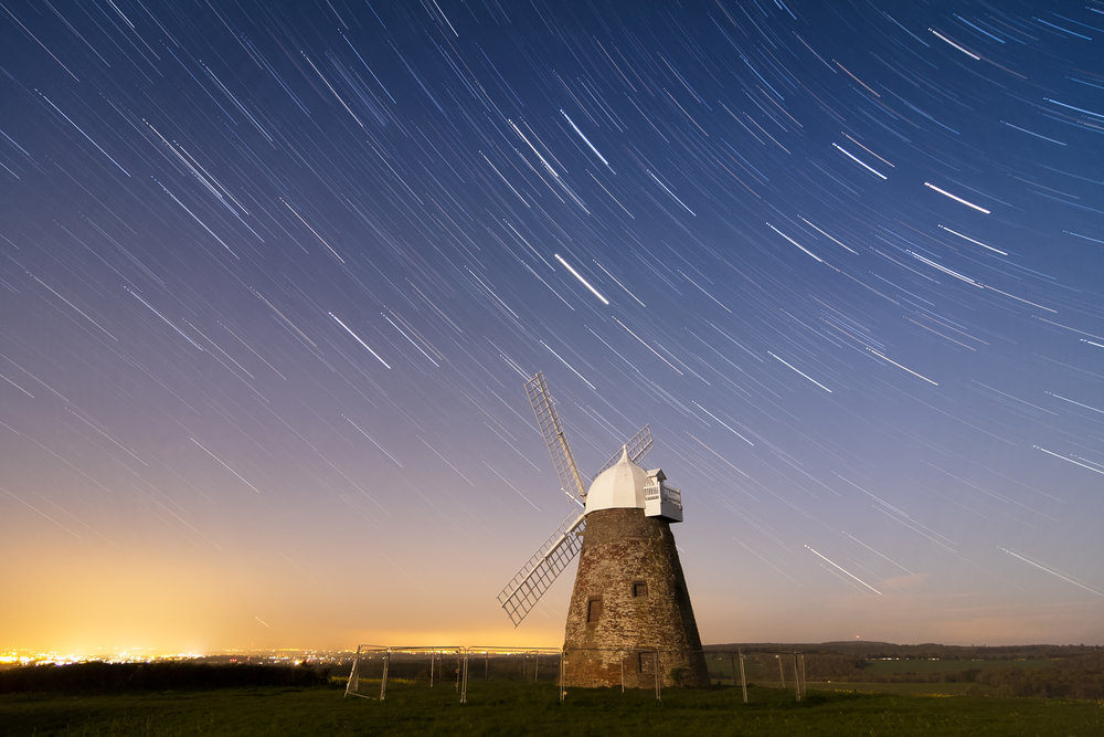 "The shutter stop controls the length of time the light sensor is exposed to the light. The photograph above allows for a long exposure creating the streaking star effect in the sky above the windmill. Since the windmill is stationary the light, although over a prolonged period of time, is emitted and recorded from the same space. In contrast, as the Earth rotates, the stars in the sky move in relation to the camera, thus changing position of the light source along the direction of the Earth's rotation. Image Attribution: "" While the sky whirls away "" by  sagesolar  is licensed under  CC BY 2.0"