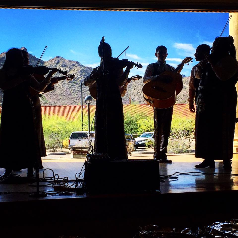 A mariachi band performing in the Curley School Auditorium, with a view of A Mountain behind them. The Auditorium features a retractable wall with beautiful views!
