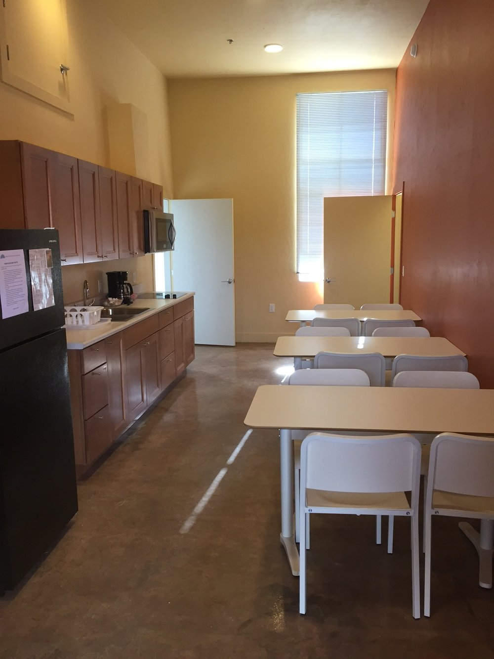Dorm suite kitchen with full-sized fridge, stove and convection oven, and seating for 12