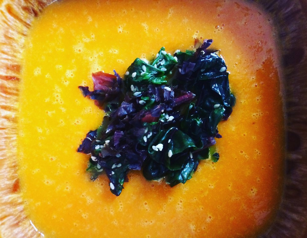 "Turmeric Sweet Potato & Carrot Soup Topped With Sautéed Sesame Dulse Swiss Chard Serves 4 Soup Dulse adds the perfect salty finish and ultimate umami experience in this puréed soup - a chilly day type of soup. 1 medium sweet potato peeled & cubed  5 carrots peeled and chopped 1-2"" chunk of ginger, minced 2"" turmeric root peel & minced OR 1 tbsp powdered 1 tsp seaweed or sea salt pepper to taste 4 cups vegetable stock or water 1tbsp coconut or oil of choice Sesame Dulse Swiss Chard 4 cups washed & sliced swiss chard greens including the stems, chopped 2 tbsp sesame seeds 2 tsp sesame oil 2 tbsp dulse flakes Heat sweet potato, salt and carrot together with coconut oil over medium-high heat and cook for 10 minutes, stirring often or until the vegetables start to brown. Add minced ginger and turmeric and cook for a further 5 minutes. Cover with stock, adding more water if needed to completely cover vegetables. Boil for 10 minutes, remove from heat and let cool. Use a high speed or immersion blender to puree the soup. Heat a large pan, adding the sesame oil, sesame seeds, and swiss chard over high heat. Toss for 2 minutes then divide between soup bowls or save the rest."
