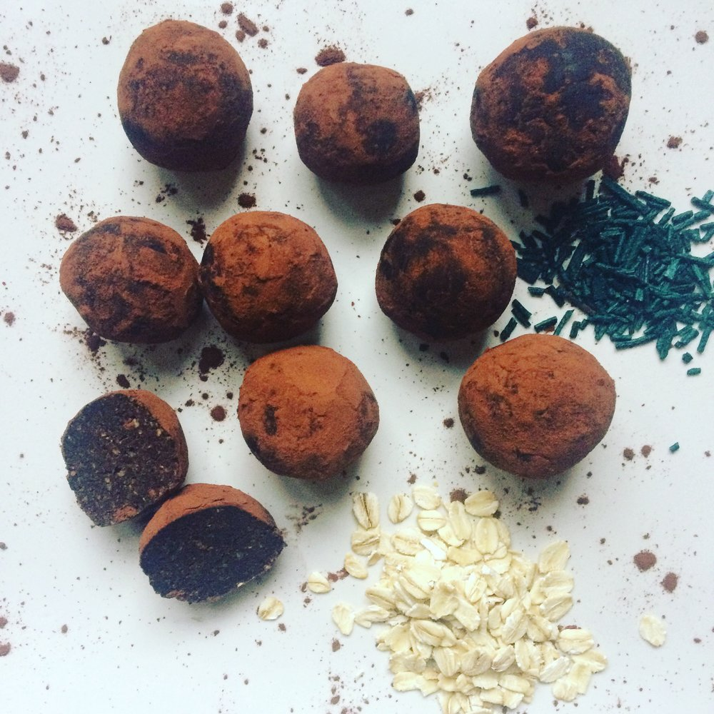 Micro Fudge Truffles       Makes 1-2 dozen    Do you have a sweet tooth? We understand! These fudge-y raw, vegan, and gluten free truffles are infused with Spirulina micro-algae and packed with fibre!  1 cup dates, pitted  1/4 cup walnuts  1/2 cup rolled oats  3 tbsp maple syrup  1 tsp pure vanilla  1 tbsp spirulina pellets or powder  1/4 cup cocoa powder +1 tbsp  Begin by adding the oatmeal to a food processor and pulsing into a course flour.  Add all remaining ingredients except cocoa and process on high for about 1-2 minute or until the mixture forms a ball in the container.  Add cocoa and process on low until the cocoa powder is well combined. Place 1 tbsp cocoa powder in a bowl and start to form your balls in desired size.  Place the formed balls one at a time into the bowl with cocoa powder and coating well before storing in the fridge in an air tight container.