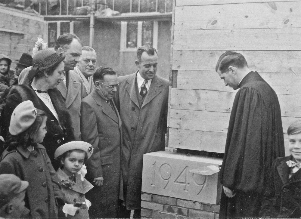 - The laying of the cornerstone for the big addition in 1949. In addition to the adult members shown here with their children, Rev. Walter Lounsbury can be seen praying over the cornerstone.