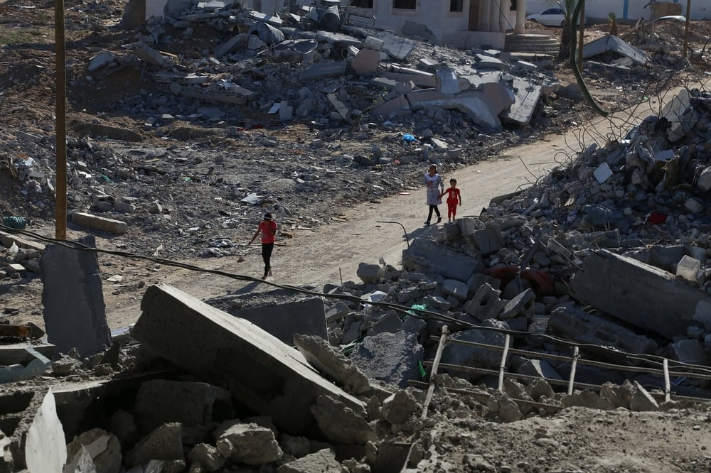 Children walking through a bombed area of Gaza.