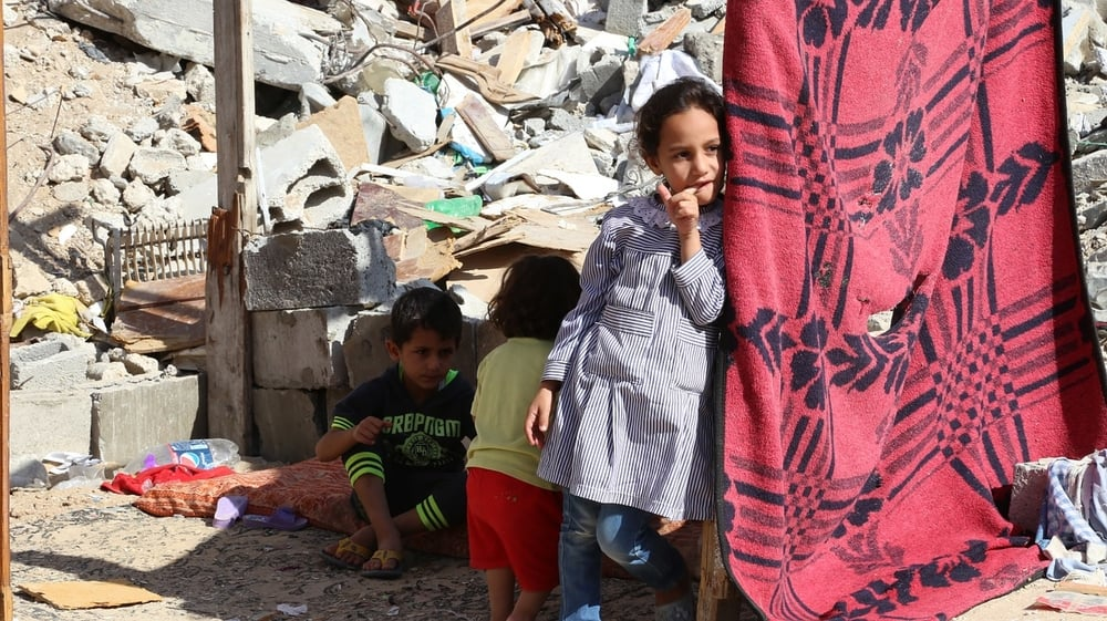 Small children rest in the shade of a blanket amid debris in Gaza.