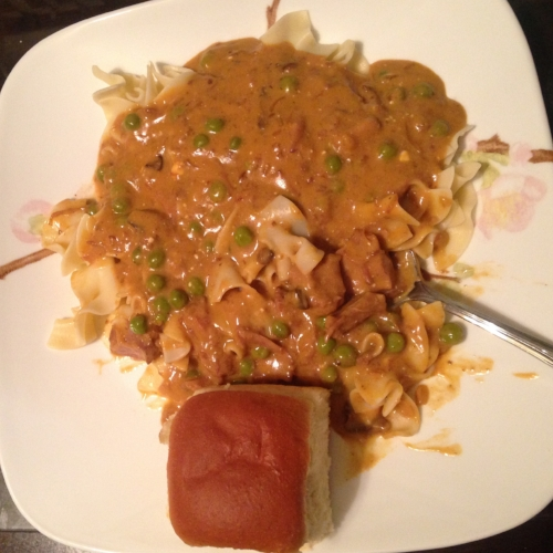 Beef stroganoff with peas and a roll