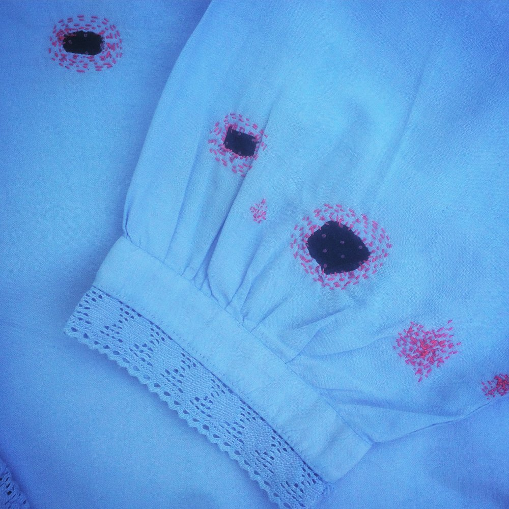 Blue Blouse -  An old, worn but still favoured fine blue cotton blouse, which was once white. The sleeves had lots of small and medium sized holes from ageing. It has been repaired with scraps of an old cotton handkerchief, itself well used, and small stitches of rose pink cotton embroidery thread. Visible signs of wear and repair