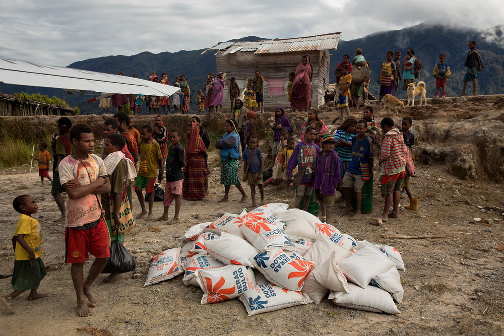 Villagers mill about after a cargo of rice is unloaded in Deneode. The rice is subsidized by the Indoneasian government, who hope to buy the good will of the papuans.