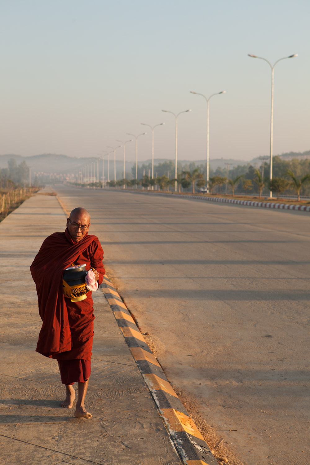 A Buddhist Monk walks down a freeway after collecting alms.