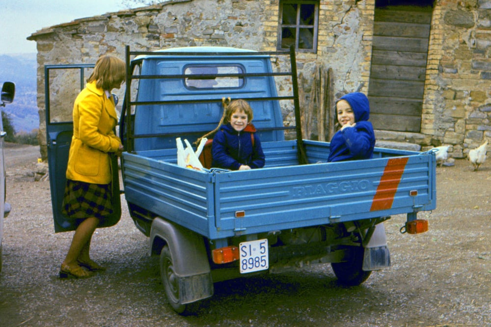 "Dan and Sally Wrightson coming back from school in a three-wheeled ""APE"" vehicle, Monteguidi, Tuscany,  1975"