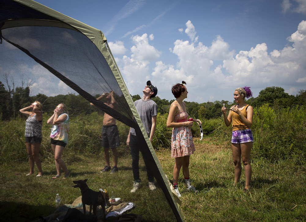 The Meredith family, left, including Tara, Samantha, Bill and Barb, from Waterman, Ill., and Adrian Torres, Summer Wheless and Devyn Maki, from Austin, Texas, watch the solar eclipse at Giant City State Park near Carbondale.