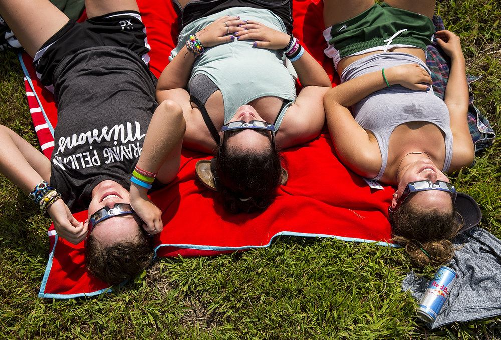 "Amanda Stiffler, left, Becca Solot and Caroline Lesniak, from Chicago, watch the solar eclipse at Giant City State Park near Carbondale. ""Everyone around was just like freaking out together,"" said Stiffler, describing the moments of totality."