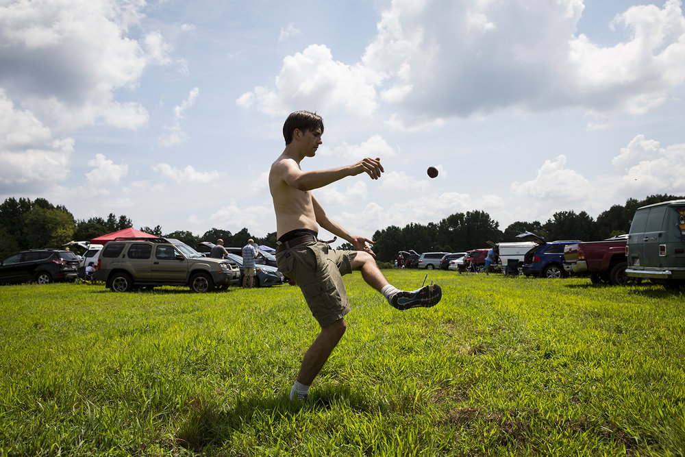 Charles Bailey, III, from Chicago, kicks up a hacky sack while waiting for the solar eclipse to begin in Giant City State Park near Carbondale.