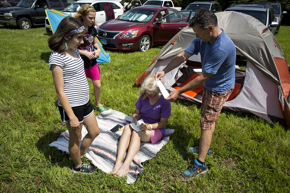 Ron Smithberger holds a piece of paper with a pinhole, casting a shadow that his wife, Shannon, outlines with a pencil to show their daughters, Lorna and Rowan the effect of the solar eclipse in Giant City State Park near Carbondale. The Smithbergers traveled from Middleton, Wis.