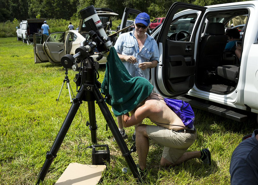 Dave Garten, an amateur astronomer from Kalamazoo, Mich., shares the view from his telescope with Eddie Villasenor, a University of Illinois student from Champaign, during the solar eclipse at Giant City State Park near Carbondale.