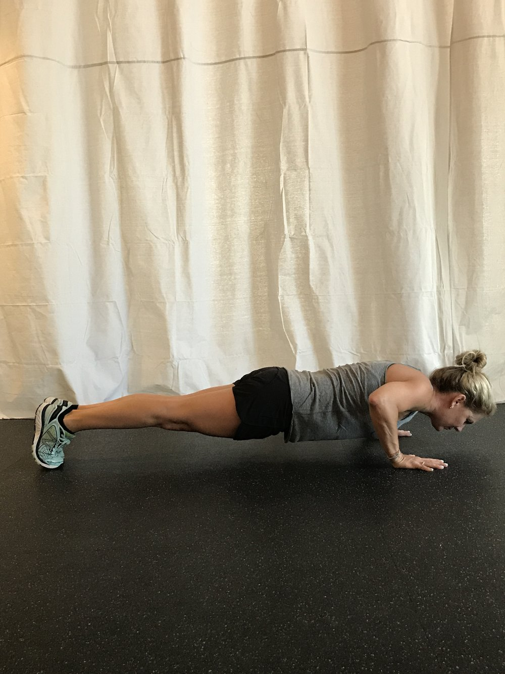 Bottom of the full pushup: core and legs engaged, hands supporting you.