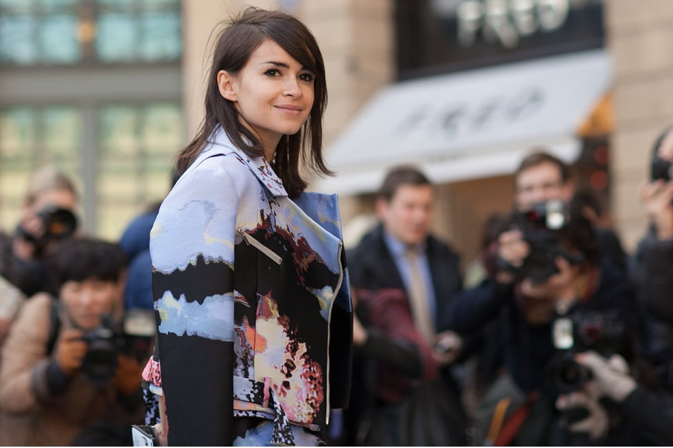 Miroslava Duma posing in front of a crowd of photographers at Paris Fashion Week. Photography Moez Achour