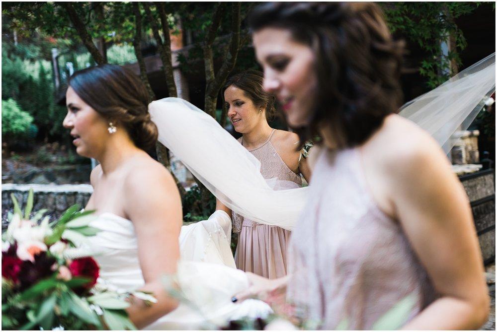 Bridesmaids walking and holding veil