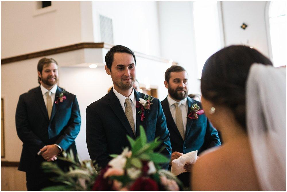 Groom looking at bride at altar