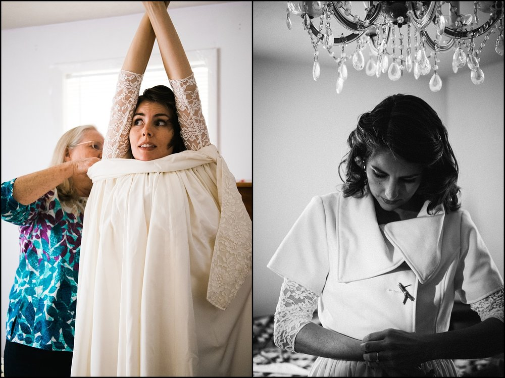 Bride putting wedding dress on with mother