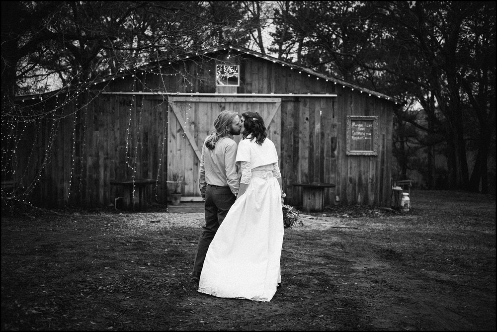 Black and white candid photo outside barn