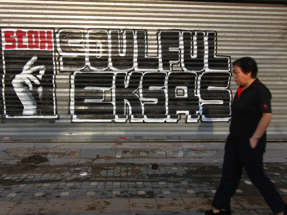 a woman walking in the streets of Beijing before a graffiti