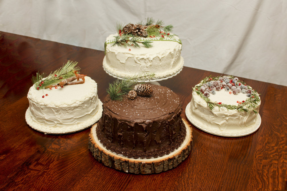 Winter themed cakes decorated with pine branches, pine cones, rosemary, cinnamon sticks, pomegranates, and sugared fruits.