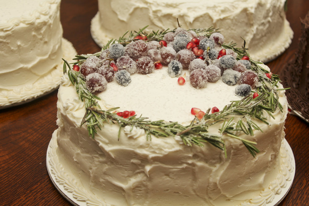 Winter themed cake decorated with rosemary, pomegranates, and sugared fruits.
