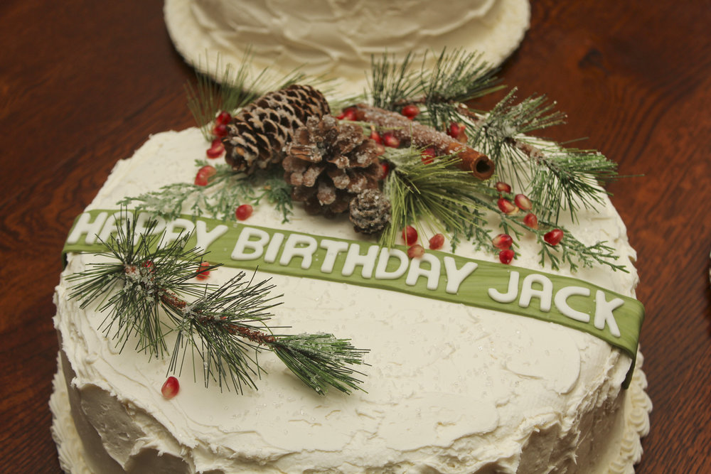 Winter themed cake decorated with pine branches, pine cones, cinnamon sticks, and pomegranates.