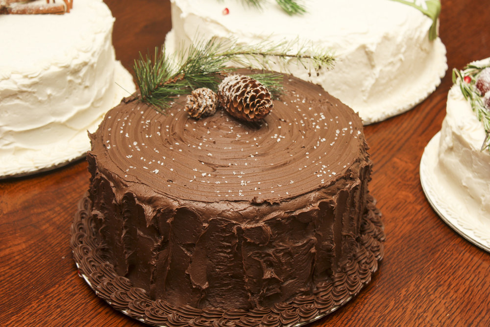 Winter themed cake decorated with pine branches and pine cones.
