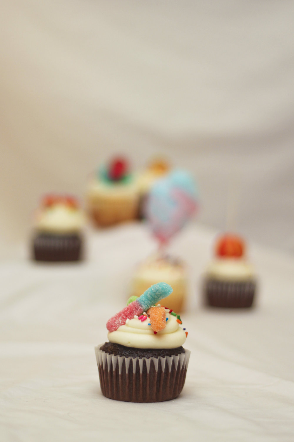 Candy themed cupcakes decorated with gummies, cotton candy, ring pops, and lollipops.