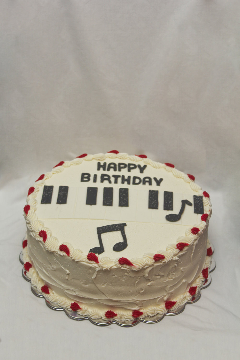Musical birthday cake decorated with music notes and piano keys made of fondant.