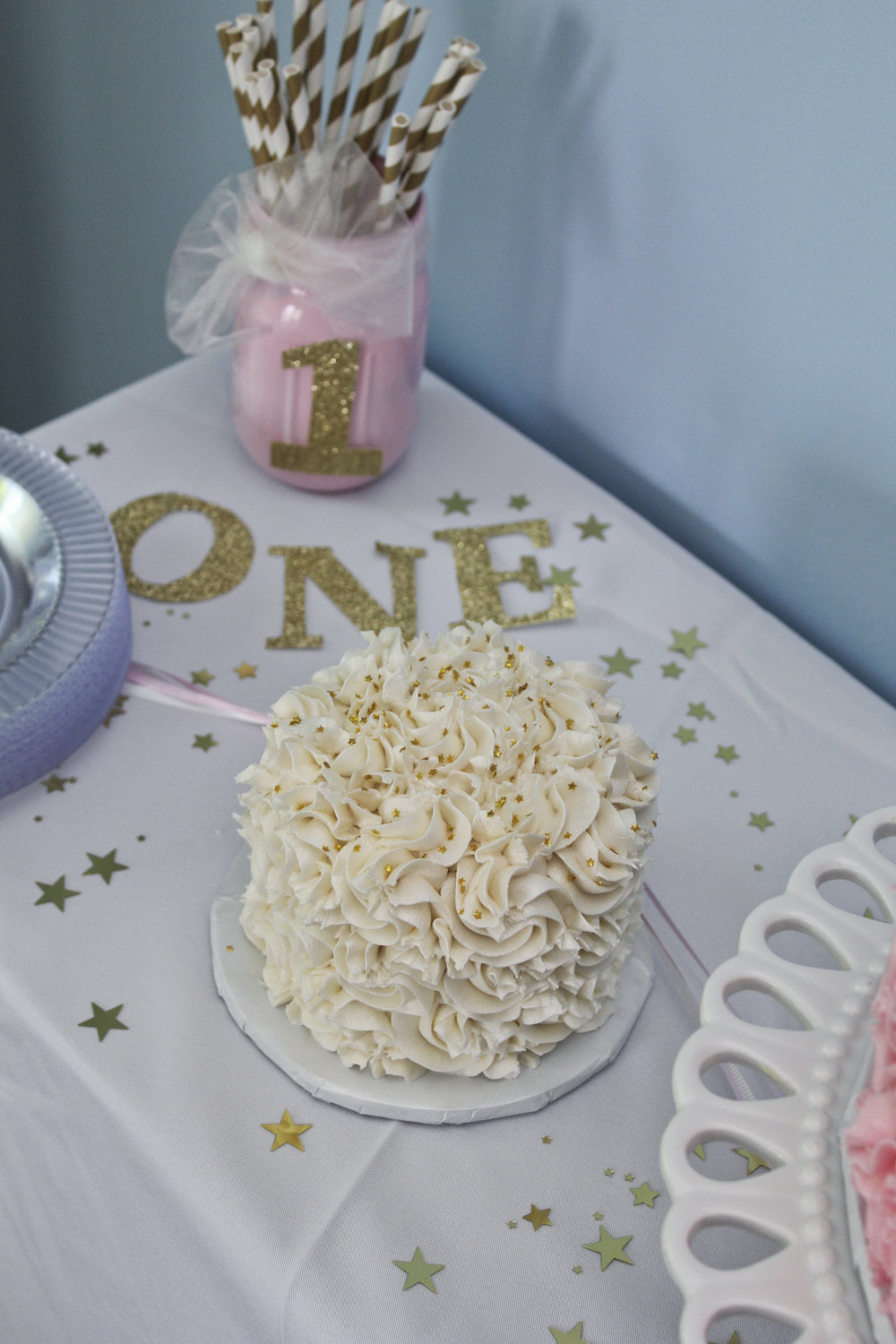 Rosette smash cake for a little girl's first birthday party. Edible gold star sprinkles are the perfect finishing touch!