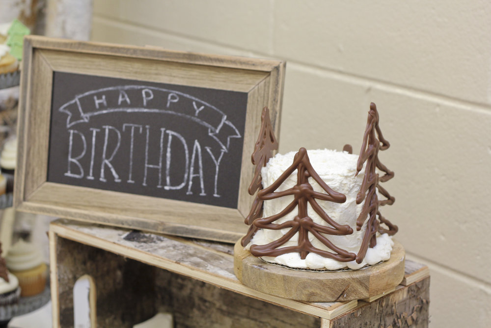 Lumberjack first birthday party smash cake decorated with chocolate pretzel trees. Perfect for this little boy's first birthday!