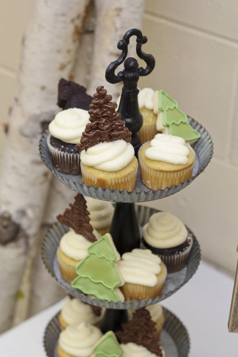 Lumberjack first birthday party cupcakes decorated with pine trees made out of melted chocolate. Pine tree shortbread cookies are the perfect compliment!