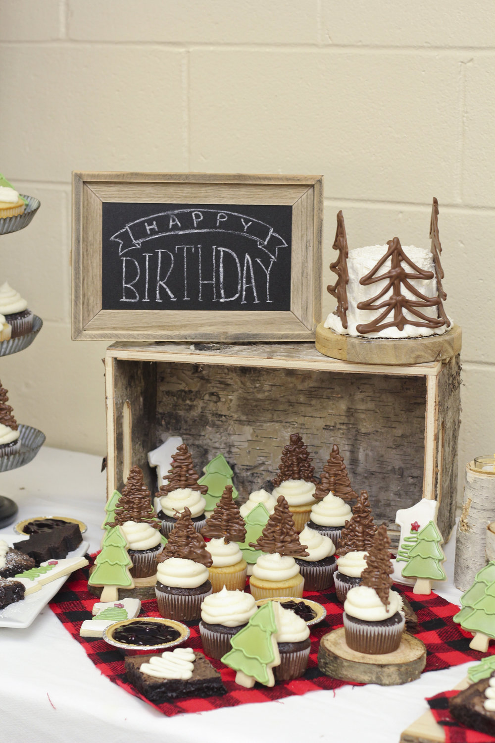 Lumberjack first birthday party smash cake with chocolate pretzel trees. Chocolate cupcakes, vanilla cupcakes, pine tree shortbread cookies, and mini blueberry pies make the perfect dessert bar for a first birthday party!