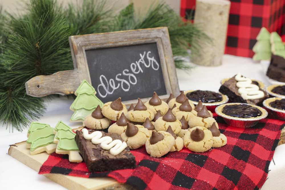 For a lumberjack first birthday party, peanut butter blossom cookies, evergreen tree cookies, brownies, and mini blueberry pies make the perfect dessert bar!