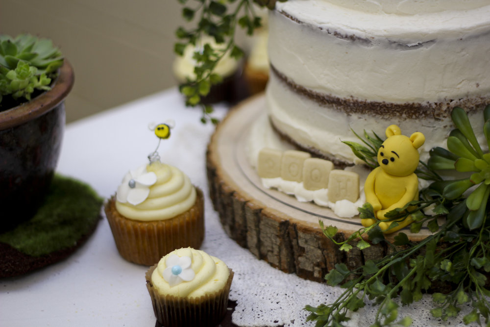 Naked cake for a pooh bear themed baby shower. Pound cake with buttercream icing decorated with succulents and a fondant pooh bear. Chocolate cupcakes and vanilla cupcakes decorated with flowers and fondant bees.
